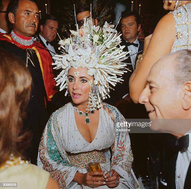 English movie star Elizabeth Taylor attends a social function wearing an elaborate headdress of pearls and fake flowers, a jewelled dress and an...