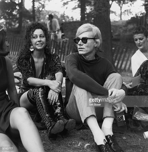 American artist Andy Warhol holding a camera and Ultra Violet a member of Warhol's Factory Superstars sitting with people in Central Park New York...