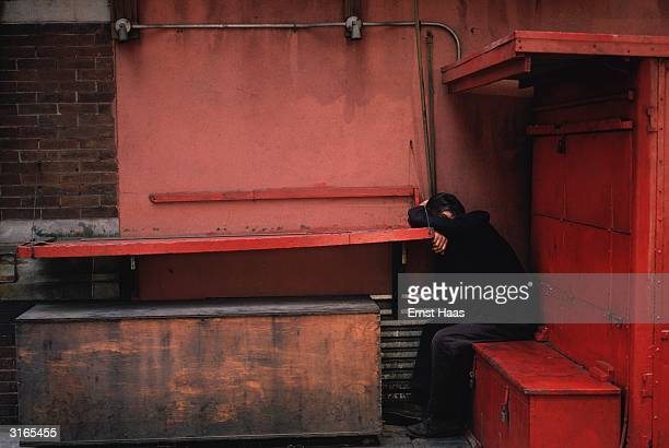 A man sits on a redpainted locker resting against a red shelf his head on his arms