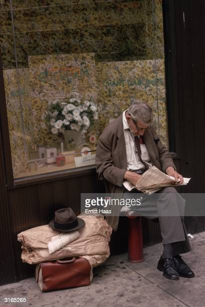 An elderly man sits outside a shop window displaying Guerlain perfume reading a paper his hat and luggage beside him