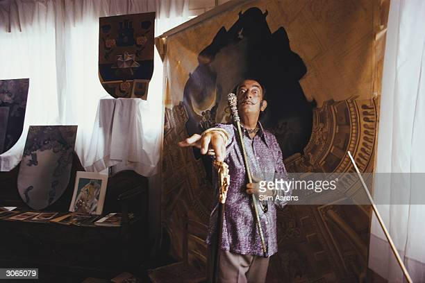 With some of his works at Port Ligat Costa Brava painter Salvador Dali in a characteristic pose with his trademark walkingstick