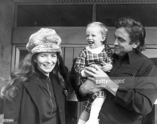 Married American country singers Johnny Cash and June Carter Cash pose with their eighteen monthold son John Glasgow Scotland June wears a knit...