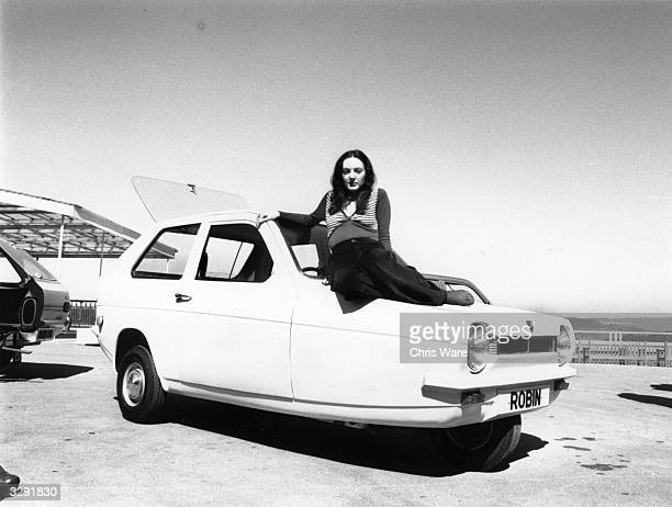 Woman sitting on the bonnet of a three-wheeled Robin Reliant car.