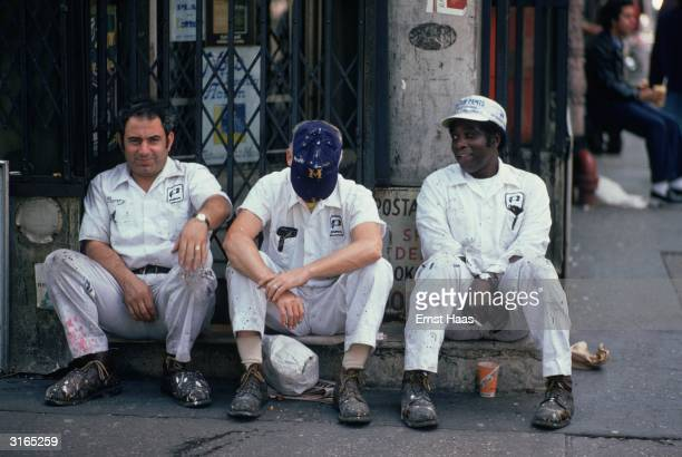 Painters in white overalls sit on the pavement as they take a break on a street in New York