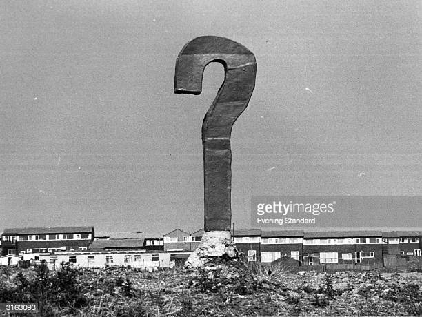 An upright piece of scrap metal and concrete forms a monumental question mark overlooking Milton Keynes Buckinghamshire