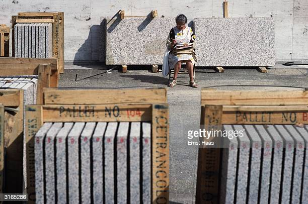 An elderly woman sits writing on a construction site surrounded by pallets containing concrete slabs