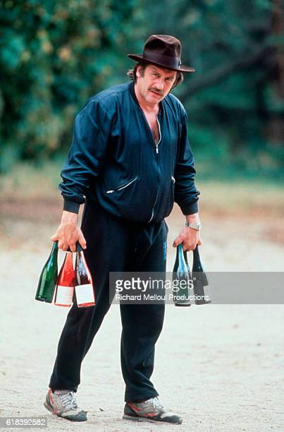 Gerard Depardieu nominated for the 1991 Best Actor Academy Award carries bottles of wine in his vineyard Chateau de Tigne