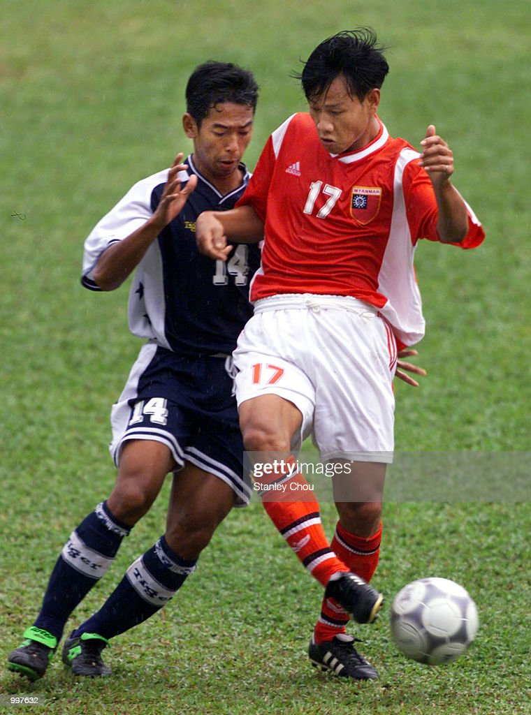 Aung Tun Naing of Myanmar is checked by Masrezwan Masturi of Singapore in a Group A match at the MPPJ Stadium, Petaling Jaya, Malaysia during the Under-23 Men Football Tournament of the 21st South East Asian Games. Myanmar won 2-1. DIGITAL IMAGE. Mandatory Credit: Stanley Chou/ALLSPORT