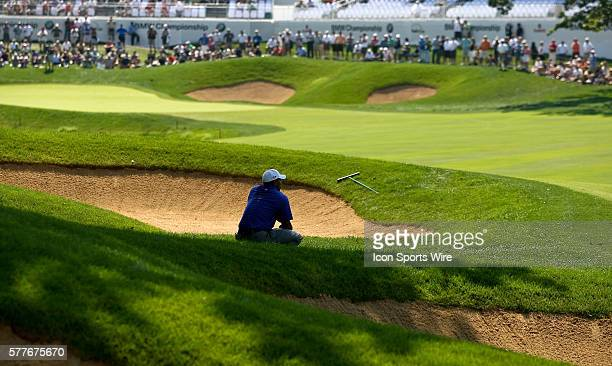 Tiger Woods takes a break as he waits his turn to hit off the fairway on hole 18 in round one of the BMW Championship at Cog Hill Golf and Country...