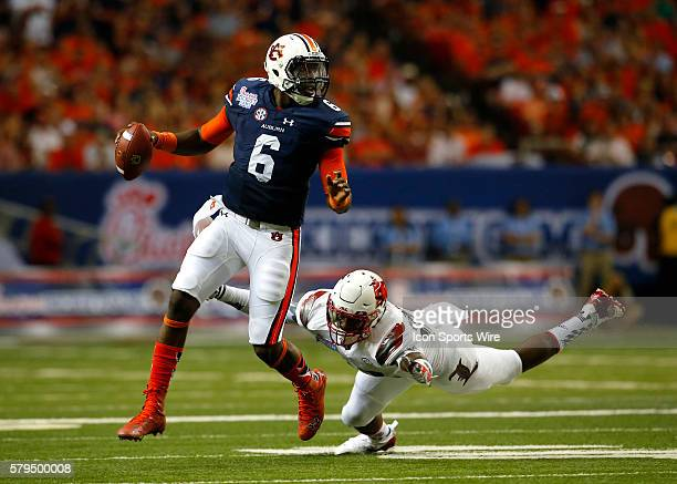 Auburn Tigers quarterback Jeremy Johnson is flushed out of the pocket by Louisville Cardinals linebacker Devonte Fields in first half action of the...