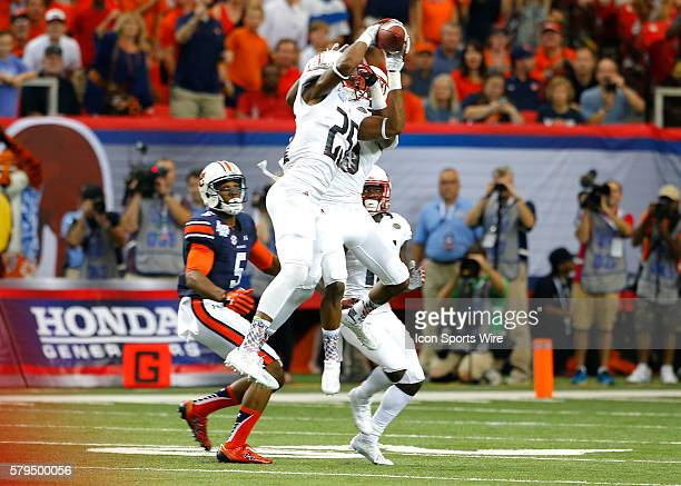 Louisville Cardinals safety Josh HarveyClemons makes an interception over Auburn Tigers wide receiver Ricardo Louis in first half action of the...