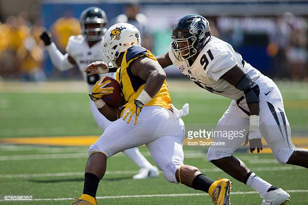 Missouri Tigers DE Charles Harris makes a tackle on West Virginia Mountaineers RB Rushel Shell III during the third quarter of the NCAA Football game...