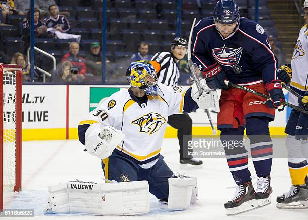 Nashville Predators goalie Marek Mazanec reaches to make a save as Columbus Blue Jackets forward Ryan Craig jumps out of the way of the puck during...