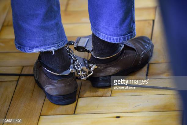 24 September 2018 BadenWuerttemberg Ravensburg One of the defendants is led into the courtroom in shackles After the assassination attempt on a...