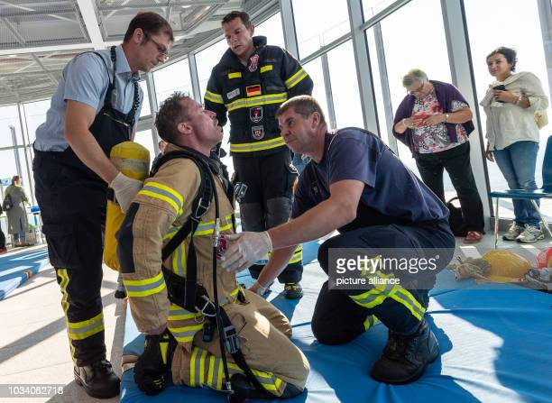 16 September 2018 BadenWuerttemberg Rottweil Firefighters take care of a colleague after he has climbed the test tower in full equipment during the...