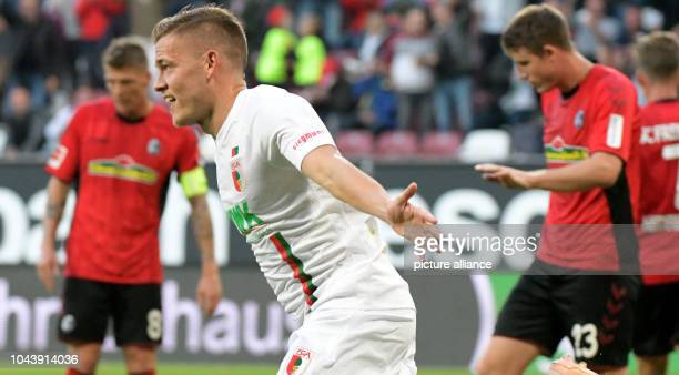 Soccer Bundesliga FC Augsburg SC Freiburg 6th matchday in the WWKArenaKArena Augsburg's Alfred Finnbogason cheers between Mike Frantz and Marco...