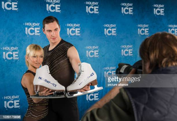 The two pair skating Olympic champions Aljona Savchenko and Bruno Massot hold ice skates in their hands during a photo shooting to promote the next...