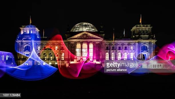 A Berliner draws colourful patterns in the evening sky with a light stick on the meadow in front of the Reichstag Photo Paul Zinken/dpa