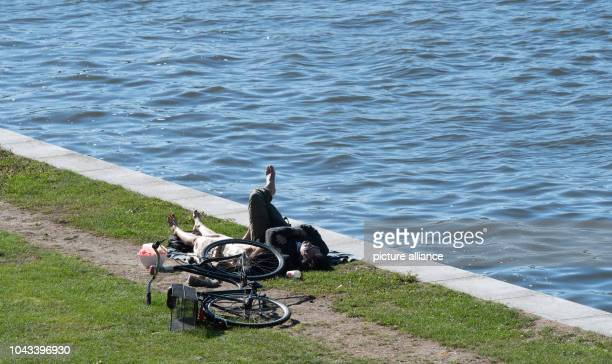 September 2018, Berlin: A woman and a man lie in the sun on the banks of the Spree in the government district. Photo: Paul Zinken/dpa