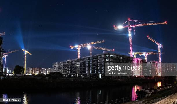 """September 2018, Berlin: Construction cranes are illuminated with coloured light during the festival """"Berlin lights up"""". Photo: Paul Zinken/dpa"""