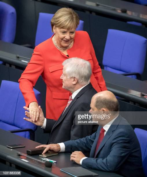 Federal Chancellor Angela Merkel greets Horst Seehofer Minister of the Interior and Olaf Scholz Minister of Finance before a plenary session of the...