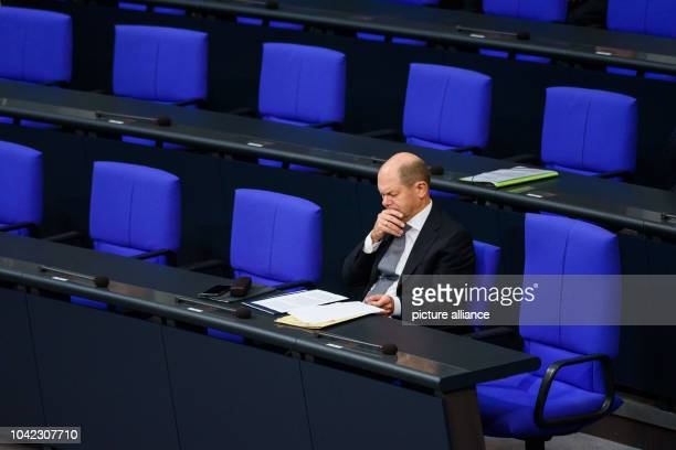 Olaf Scholz Federal Minister of Finance sits in his seat on the government bench before the start of a plenary session of the German Bundestag Among...