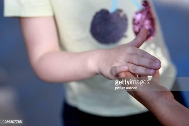 Two girls are holding hands Photo Britta Pedersen/dpaZentralbild/dpa