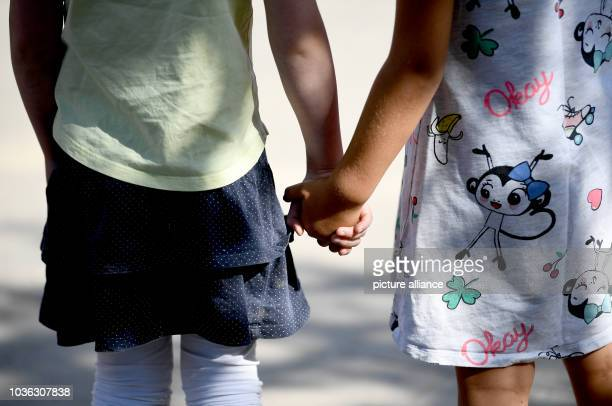 September 2018, Berlin: Two girls are holding hands. Photo: Britta Pedersen/dpa-Zentralbild/dpa