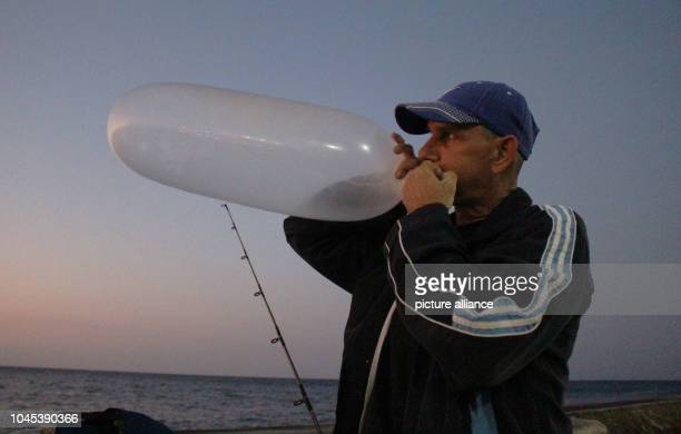 A pescador infla un preservativo para usarlo de flotador del anelo Todas las tardes cuando empieza a caer el sol Ernesto Rodríguez se sienta en el...