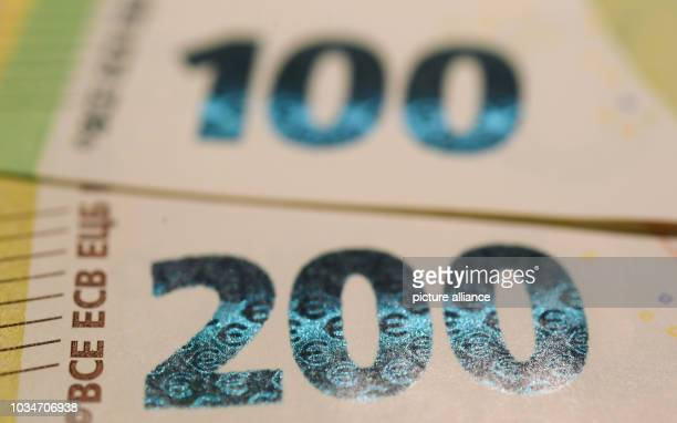 September 2018, Hessen, Frankfurt/Main: Small euro signs can be seen in the figures of the revised 100 and 200 euro banknotes during the presentation...