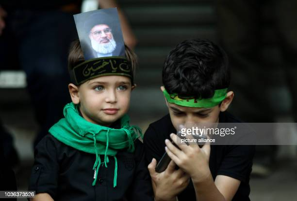 A boy wearing a headband with the picture of SecretaryGeneral of Hezbollah Hassan Nasrallah sits next to another boy during a rally of the supporters...