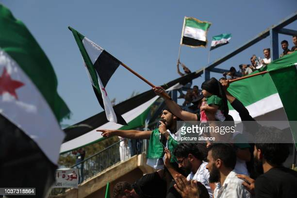 A Syrian protester speaks to the crowd during a mass demonstration against the Syrian regime of Bashar alAssad in Saraqib east countryside of the...