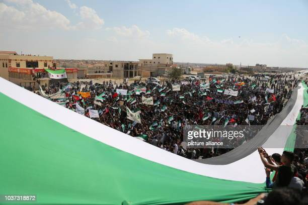 Syrian protesters wave a giant opposition flag during a mass demonstration against the Syrian regime of Bashar alAssad in Saraqib east countryside of...