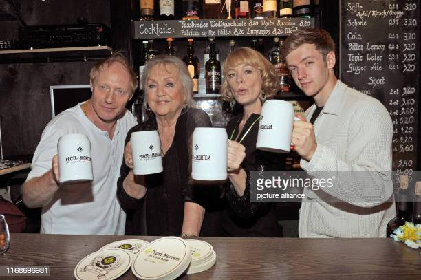 The actors Simon Schwarz Doris Kunstmann Elke Winkens and Timur Bartels stand with beer mugs in their hands behind the counter of a bar in the...