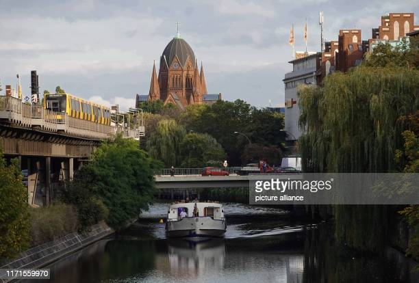 """September 2019, Berlin: A subway line 1 leaves Möckernbrücke station in the direction of Hallesches Tor. The excursion ship """"Spree-Athen"""" of the..."""