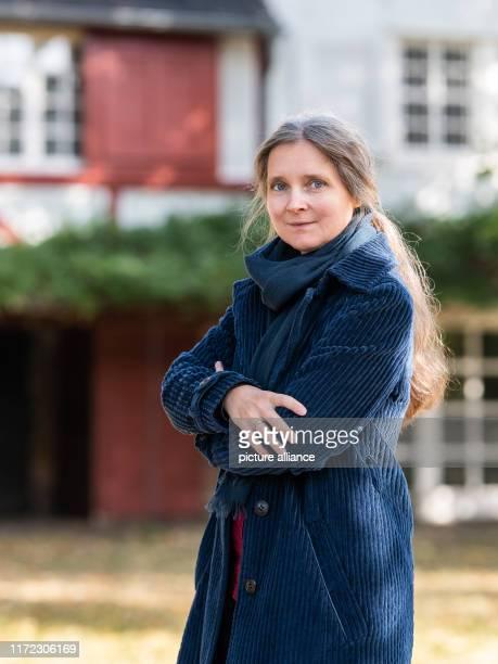 September 2019, Hessen, Lahntal-Goßfelden: Marion Poschmann, author, looks into the photographer's camera in the garden of the Ubbelohde House. The...