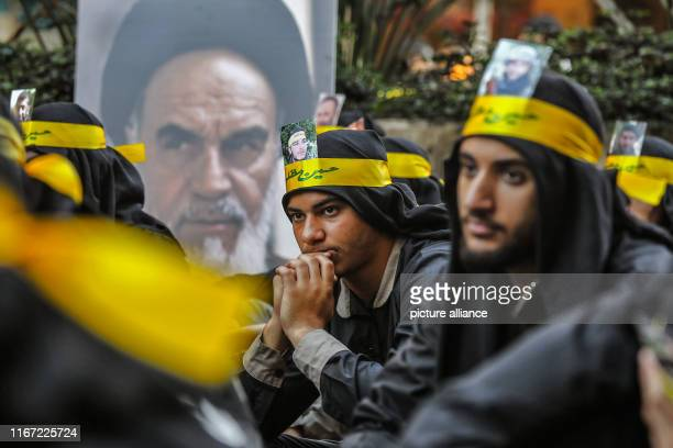 September 2019, Lebanon, Beirut: Supporters of Hezbollah, the Shia pro-Iranian political party and militant group, sit next to a poster of Ayatollah...