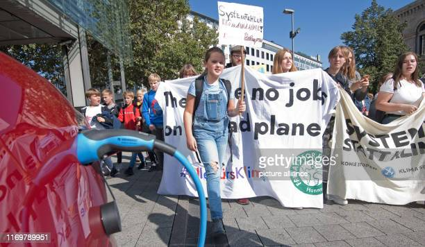 September 2019, Lower Saxony, Hanover: Demonstrators walk past an electric vehicle Tesla Model S, which is currently being charged. The demonstrators...