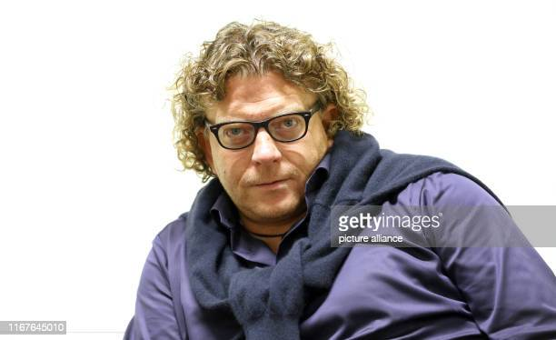 September 2019, Mecklenburg-Western Pomerania, Rostock: Marcus Bosch, artistic director of the Norddeutsche Philharmonie, sits in front of a...