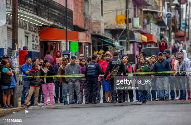 September 2019, Mexico, Naucalpan: Policemen prevent neighbours from approaching the body of a young man shot dead in Naucalpan. Insecurity, crime...