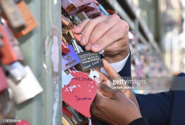 September 2019, North Rhine-Westphalia, Cologne: The actor Jo Weil and the singer Aisata Blackman install a love castle on the Hohenzollern Bridge in...