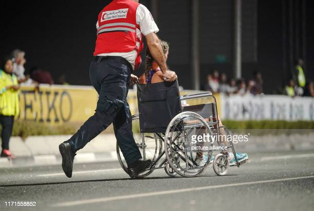 September 2019, Qatar, Doha: Athletics, World Championships, Marathon, Women. Paramedics bring an exhausted runner with a wheelchair off the track....