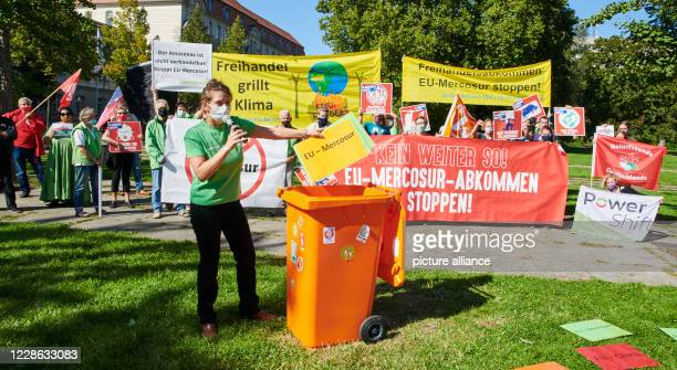 "September 2020, Berlin: Gesche Jürgens, a Greenpeace activist, symbolically throws a poster with the inscription ""EU-Mercosur"" into the trash can...."