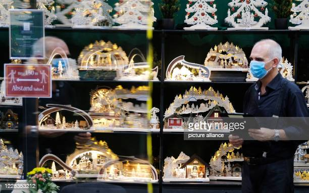 September 2020, Saxony, Leipzig: An employee of a wood art company at his stand, which is equipped with Plexiglas panels. For half a year, the Corona...