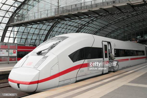 September 2021, Berlin: A man pushes a bicycle into the bicycle compartment in a Deutsche Bahn ICE train at Berlin Central Station. Deutsche Bahn and...