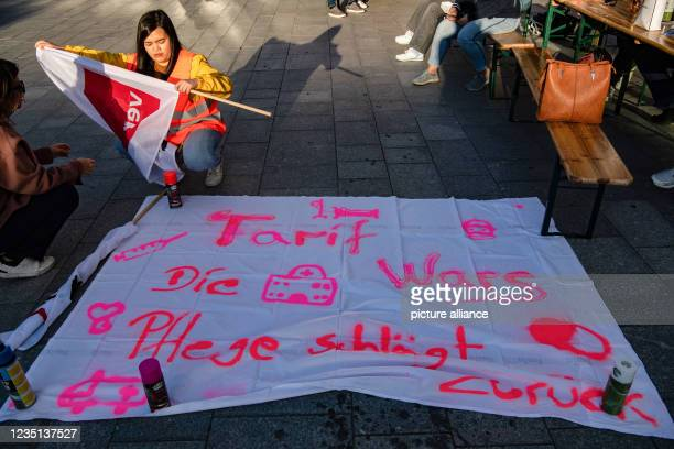 September 2021, Berlin: A striker kneels in front of a banner in the Charité ward block. This morning, the employees of the state-owned Berlin...