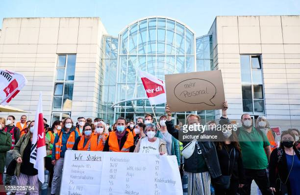 """September 2021, Berlin: """"More staff"""" and a listing of the striking hospital wards are written on posters by nurses in front of the Glass House at..."""