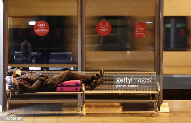 September 2021, North Rhine-Westphalia, Cologne: A man sleeps in the main station while a train pulls in. The German Train Drivers' Union ended its...