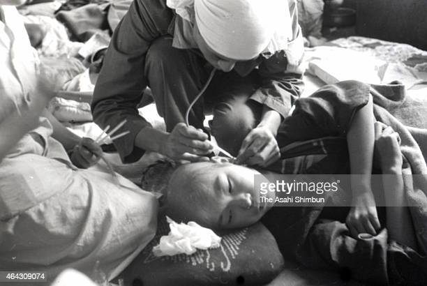 Child survivor receives treatment at a temporary hospital, set up at Shin Kozen Elementary School in Nagasaki after the atomic bombing of the...
