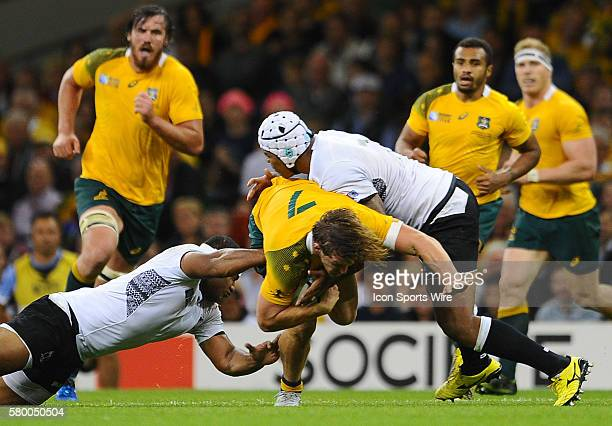 Australia's Michael Hooper is tackled by Fiji's Talemaitoga Tuapati and Akapusi Qera during the 2015 Rugby World cup match-up between Australia and...